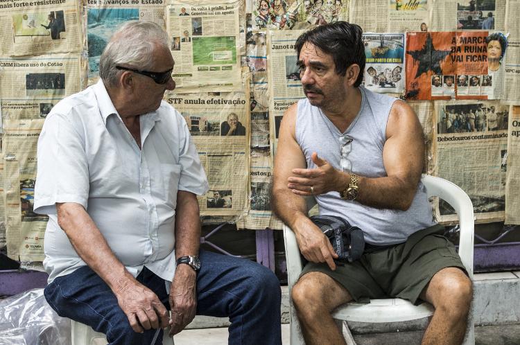 Twee mannen in Manaus voor een muur vol kritische artikelen en slogans over WK - Foto: Cornell Evers