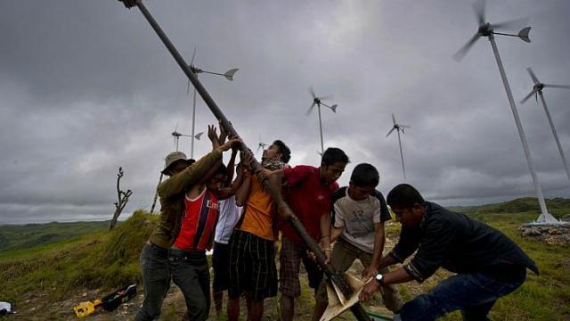 Inwoners van Sumba zetten een nieuwe windturbine neer in het dorpje Kamanggih Copyright: AFP