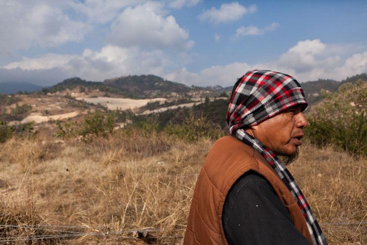 Francisco Bámaca (55) strijdt tegen de Marlin-mijn. Lopend over zijn perceel is de mijn op de achtergrond zichtbaar en omringt het hele gebied. Beeld: Michael Rhebergen