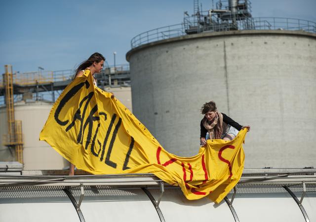 """Actievoerders van het Franse team Jedi for Climate bevestigen een spandoek met de tekst """"Cargill kills the Climate"""" aan een tank. Beeld Marten van Dijl"""