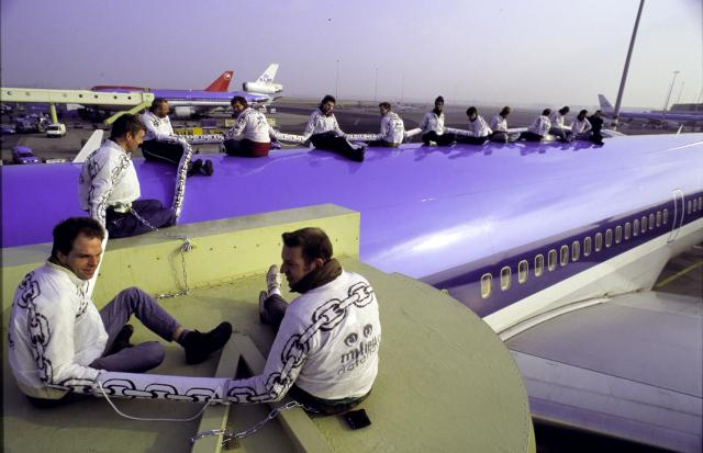 Dertien actievoerders van Milieudefensie beklimmen de romp van een vliegtuig en houden het twee uur lang bezet. Beeld Michiel Wijnbergh